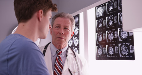 Young male adult caucasian reviewing brain xrays with mid aged p