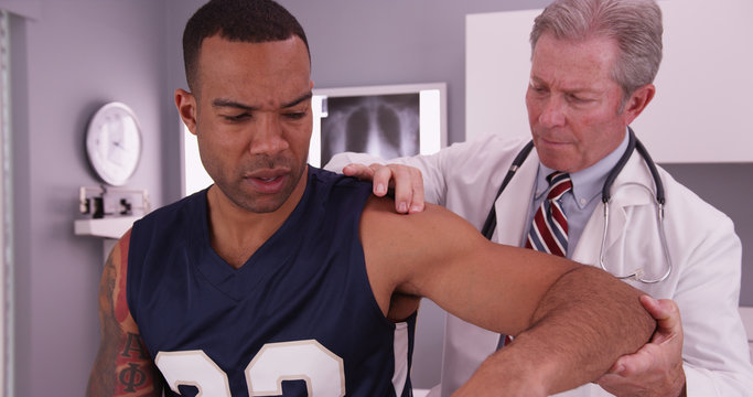 Middle aged male physician treating young male adult athlete's i