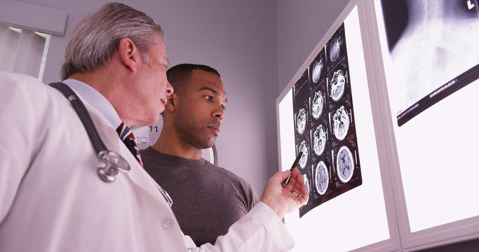 Mid aged medical doctor reviewing x ray of african patient