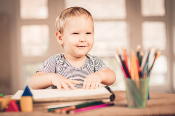 Blond boy laughing and crayons in front
