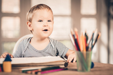 Blond boy and crayons in front of him