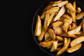 Fried potatoes on a black frying pan