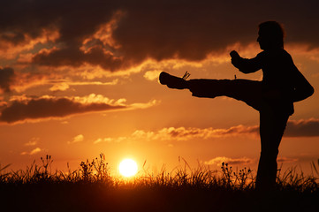 Man practicing karate on the grassy horizon at sunset. Karate kick leg. Art of self-defense. Silhouette on a background of dramatic clouds at sunset.