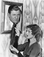 Woman adjusting tie of man in picture frame
