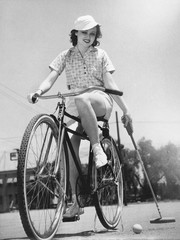 Woman on a bicycle playing polo