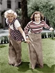 Two women playing a game of potato sack racing
