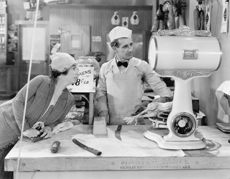 Woman standing in a butcher store looking at the scale