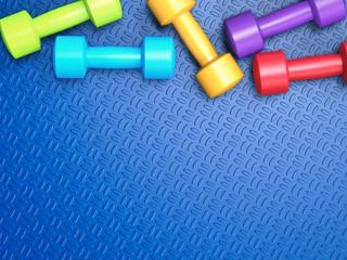 colourful dumbbells on blue background