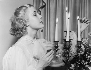 Portrait of woman lighting candles