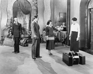 Four people standing in a the lobby of a hotel with luggage