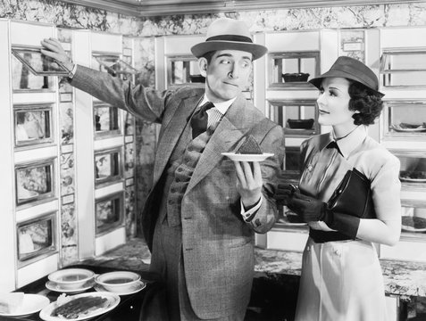 Man serving a dish to a woman in a Automat