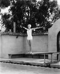 Woman on diving board at swimming pool
