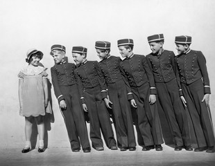 Line of young bellhops smiling at girl