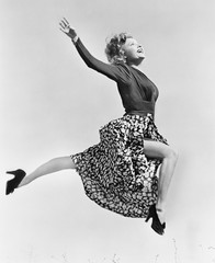 Woman in a flowing skirt leaping through the air
