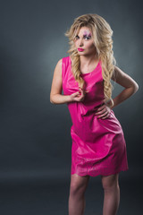 sexy blonde girl with art makeup posing in the studio on a dark background wall. Pink image. Makeup with flowers.