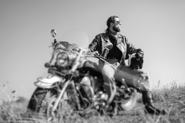 Portrait of a young man with beard sitting on his cruiser motorcycle and looking to the sun. Man is wearing leather jacket and blue jeans. Low point of view. Tilt lens blur effect. Black and white