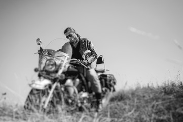 Portrait of a young biker with beard sitting on his cruiser motorcycle and looking to his bike. Man is wearing leather jacket and blue jeans. Low point of view. Tilt lens blur effect. Black and white