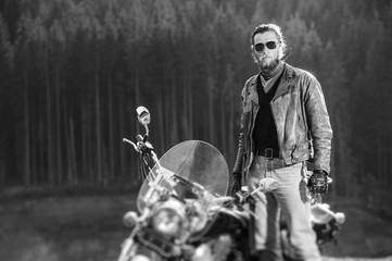 Portrait of handsome biker with beard standing by his custom made cruiser motorcycle on a sunny day with forest on the background. Tilt shift lens blur effect. black and white