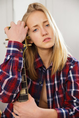 Portrait of young blonde girl with a guitar