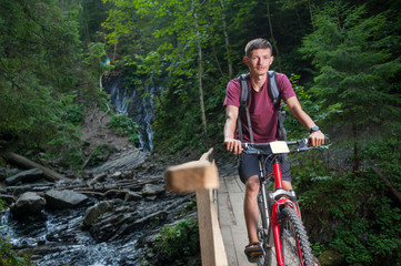 Young man on wooden bridge crossing the mountain river on his bike and looking at the camera in the forest
