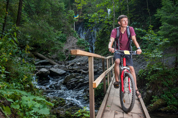 Young man on wooden bridge crossing the mountain river on his bike and looking up