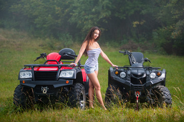 Beautiful woman standing between two four-wheelers ATV. Smiling and looking towards the camera