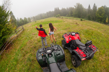 Happy beautiful couple standing near four-wheelers ATV. Man pointing into the distance foggy nature. Wide view from high piont