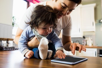 Cute mother showing tablet to her baby
