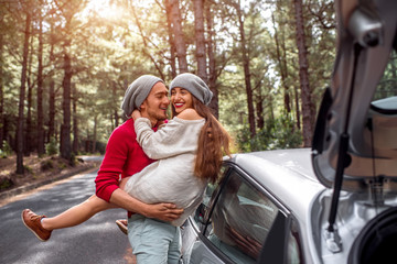 Young and lovely couple in sweates and hats having fun hugging together near the car on the roadside in the pine forest