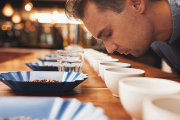 Man smelling aromatic coffee at a tasting
