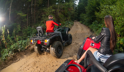 Couple driving four-wheelers ATV offroad. View from the back