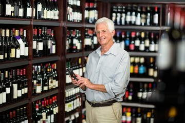 Smiling senior man choosing wine