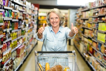 Smiling senior woman with cart showing thumbs up
