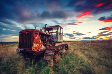 Beautiful sunset over field and old rusty tractor