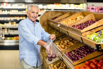 Smiling senior man buying red onions at the grocery shop