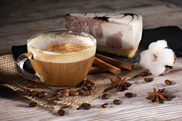 cup of coffee with milk and cheesecake on a wooden background.
