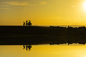 silhoutte of a man standing with his bike during beautiful golde