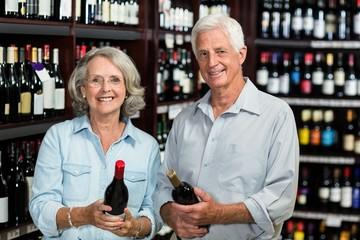 Smiling senior couple choosing wine at the supermarket