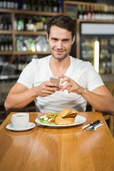Handsome man taking a picture of his food