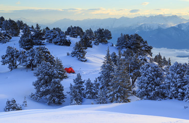 Fotomurales - Red tent in the snow covered mountains during a nice sunrise.