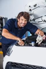 Happy Mechanic Examining Car Engine