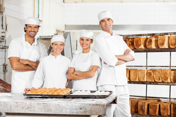 Confident Baker's Standing At Table In Bakery