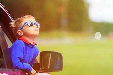 happy little boy travel by car in summer
