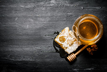 Wall Mural - Honey background. Natural honey comb and a glass jar.