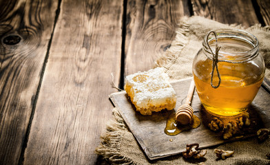 Wall Mural - Sweet honey in the comb, glass jar with nuts.