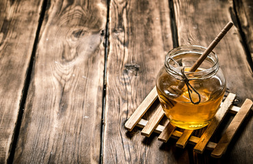 Glass jar with natural honey and a spoon.