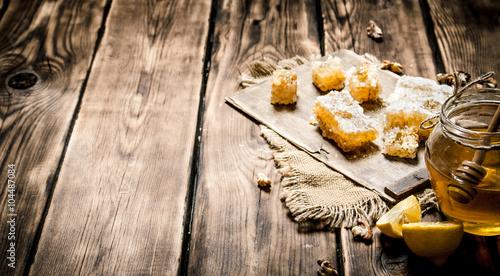 Wall mural Honey background. Natural honey lemon slices and walnuts.