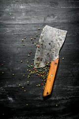 Pepper , spices and an old hatchet. On black rustic background.