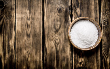 Wooden Cup with salt . On wooden background.
