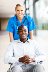 medical nurse with male patient in wheelchair
